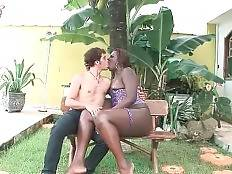 Cute white fellow and dark chocolate tranny are kissing outdoor.
